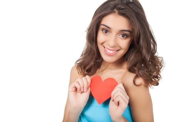 Ik ben verliefd. aantrekkelijke jonge vrouw die een rood papieren hart vasthoudt en naar de camera glimlacht terwijl ze op een witte achtergrond staat