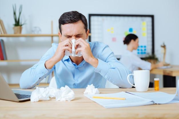 Ik ben ziek. pessimistische man die de ogen gesloten houdt en een servet in beide handen houdt terwijl hij zijn ellebogen op tafel legt