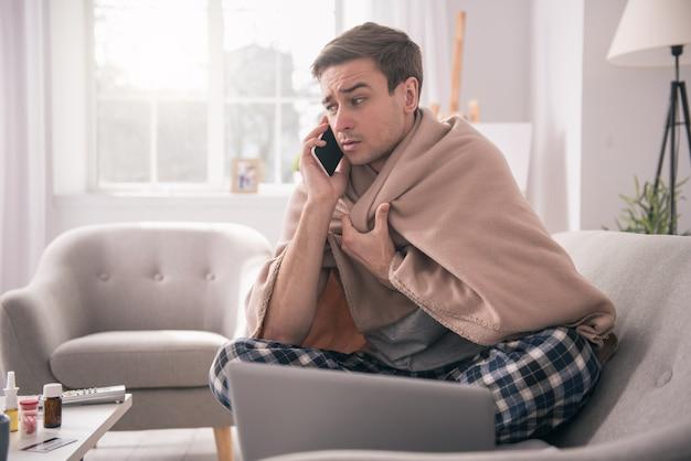 Ik ben ziek. trieste jongeman praat aan de telefoon met zijn werkgever terwijl hij vraagt naar het ziekteverlof