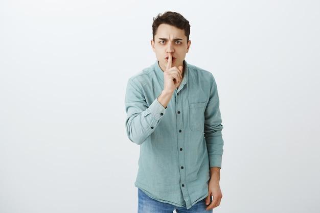 Ik beveel je stem te dempen. portret van ontevreden ernstige jonge man in trendy shirt