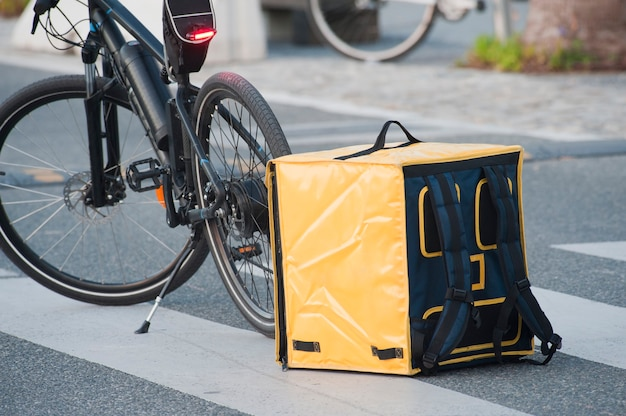 Ik bezorg eten aan huis een gele transport thermische zak met een fiets op de achtergrond in de stad