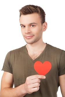 Ik denk dat ik verliefd ben. knappe jonge man die een papieren hart vasthoudt en glimlacht terwijl hij op een witte achtergrond staat