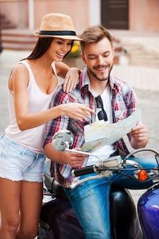 Ik denk dat we er zijn! mooie jonge verliefde paar samen op scooter zitten en kaart onderzoeken terwijl vrouw erop wijst en glimlacht