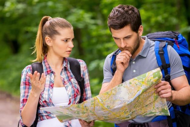 Ik denk dat we verloren hebben. nadenkende jonge man met rugzak die kaart onderzoekt terwijl boze vrouw bij hem in de buurt staat en gebaren maakt