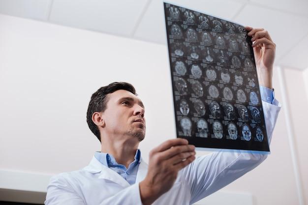Ik doe mijn werk. hardwerkende ervaren serieuze oncoloog die in het laboratorium staat en een mri-scanafbeelding vasthoudt terwijl hij aan het werk is