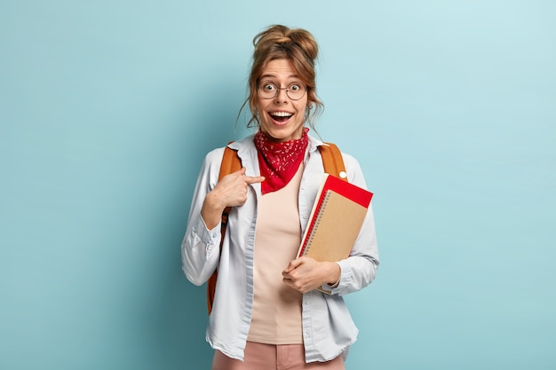 Ik, echt? blij lachend europese vrouw wijst naar zichzelf, glimlacht breed, kan niet geloven in geslaagd examen, poseert met blocnote