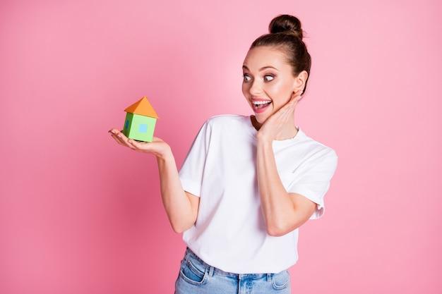 Ik ga dit huis kopen. foto van aantrekkelijke dame houdt een klein papieren huis vast voor een lage prijs