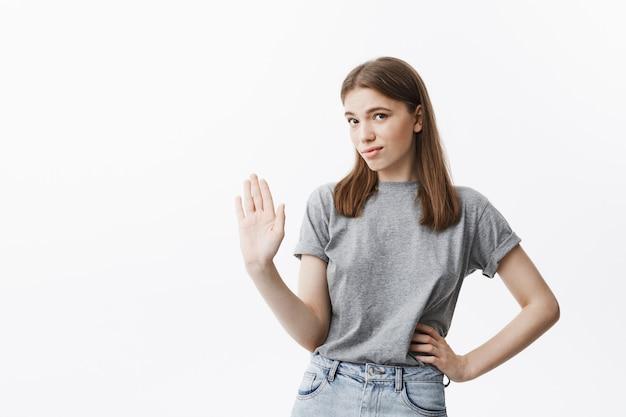 Ik ga er niet over praten. portret van knappe zelfverzekerde blanke meisje met bruin haar gebarend met de hand, waaruit blijkt dat ze niet wil luisteren naar haar vriendje dat probeert uit te leggen dat hij niet vals speelt.
