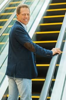 Ik ga naar boven. vrolijke volwassen man die over de schouder kijkt en glimlacht terwijl hij omhoog gaat met de roltrap