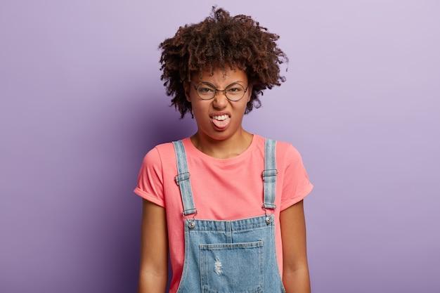 Ik ga niet met je praten. ontevreden afro-amerikaanse vrouw mokkend van ongenoegen, steekt tong uit