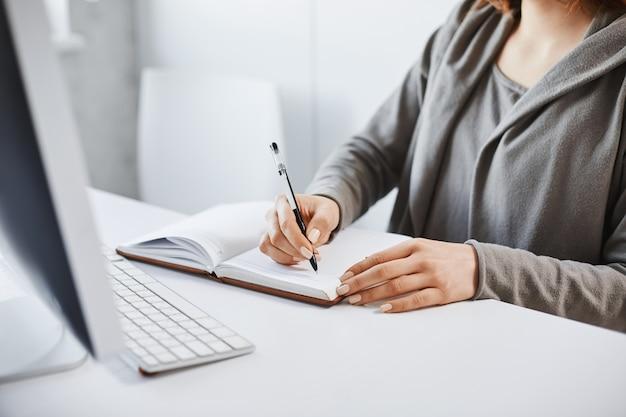 Ik geef de voorkeur aan een ouderwetse schrijfmethode. bijgesneden portret van drukke vrouw maken van aantekeningen in notitieblok, kijken naar computerscherm tijdens werktijd op kantoor, proberen te concentreren en te concentreren op opdracht