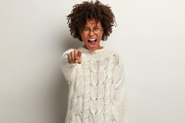 Ik geef jou de schuld! stressvolle afro-amerikaanse vrouw met knapperig, borstelig haar wijst direct wijsvinger, schreeuwt woedend, uit ergernis, staat over witte muur, zegt dat je schuldig bent
