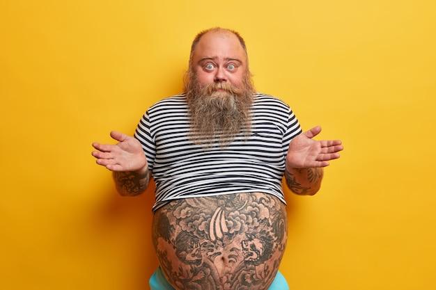 Ik geef niet om regels. onverschillige onzorgvuldige ondervraagde man met baard haalt zijn schouders op met aarzeling, verbaasd over domme vraag, heeft een zeer grote buik, draagt een gestreept t-shirt, geen idee hoe het is gebeurd
