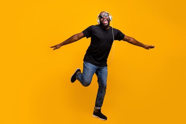 Ik geloof dat ik kan vliegen. full size phtoo van grappige positieve afro-amerikaanse man luisteren muziek met headset zingen lied hand in hand als vogels vleugels dragen t-shirt sneakers geïsoleerde felle kleur muur