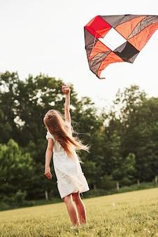 Ik geloof dat ik kan vliegen. gelukkig meisje in witte kleren veel plezier met vlieger in het veld. prachtige natuur.