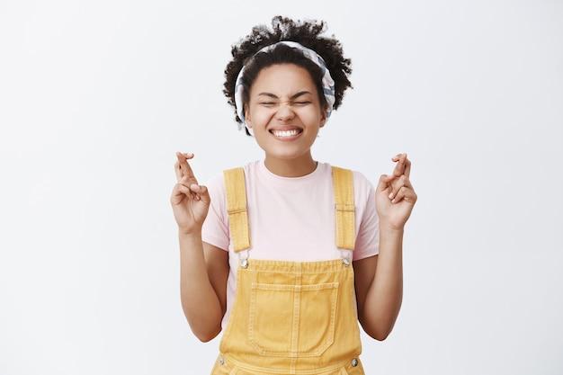 Ik geloof in wonderen. grijnzende knappe vrolijke afro-amerikaanse vrouw in gele overall en hoofdband, ogen sluitend en breed glimlachend, vingers gekruist en intens verlangend dat een droom uitkomt