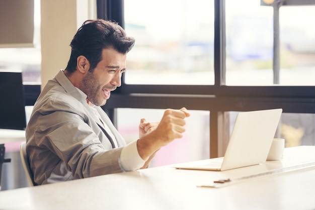 Ik heb de uitdaging voltooid een zeer gelukkige zakenman gebruikt een laptop op kantoor