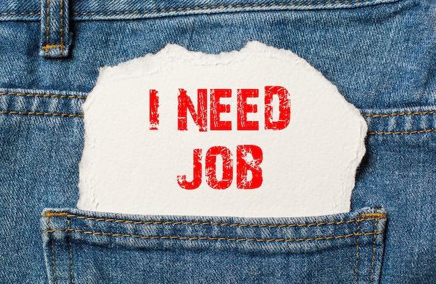 Ik heb een baan nodig op wit papier in de zak van een blauwe spijkerbroek