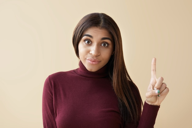 Ik heb een idee! bijgesneden beeld van aantrekkelijke emotionele jonge donkere vrouw die grappige gezichtsuitdrukking maakt en wijsvinger omhoog wijst om je aandacht te trekken, opgewonden verrast kijken