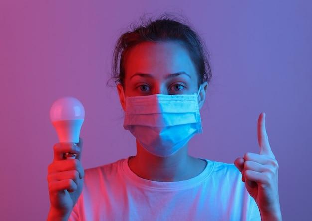Ik heb een idee! vrouw met medisch gezichtsmasker met gloeilamp in rood-blauw neonlicht holding