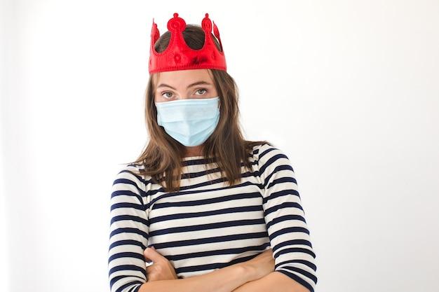 Ik heb een kroon. vrouw in een rode kroon en een beschermend masker. gekroonde persoon werd ziek met het virus