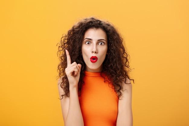 Ik heb een uitstekend plan. enthousiaste, emotionele en opgewonden vrouw met krullend kapsel in oranje bijgesneden top die wijsvinger opheft in eureka-gebaar die lippen vouwt die ogen knallen en geweldige suggestie toevoegt.