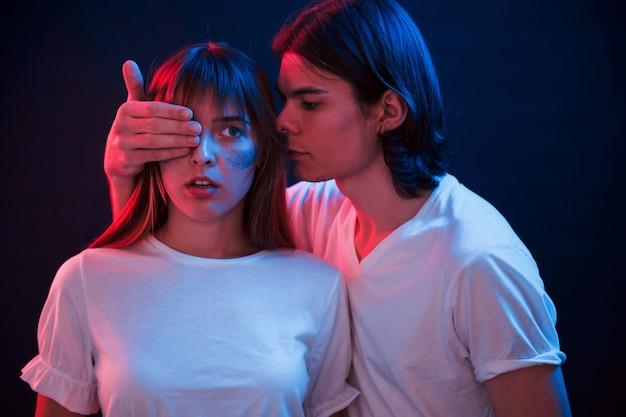 Ik heb een verrassing voor je. paar dat zich in donkere ruimte met rode en blauwe neonverlichting bevindt