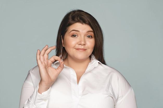 Ik heb het begrepen. foto van vriendelijk ogende charmante jonge blanke vrouw met overgewicht gekleed in formeel wit overhemd glimlachend vol vertrouwen, ok gebaar makend alsof ze zeggen dat alles in orde is