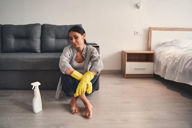 Ik heb het gedaan. jonge vrouwelijke persoon die op de grond zit terwijl ze pauzeert tijdens haar schoonmaakactiviteit