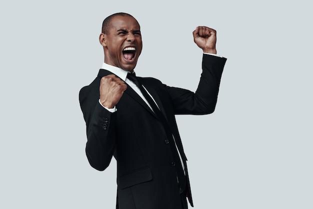 Ik heb het gedaan! knappe jonge afrikaanse man in formalwear gebaren en schreeuwen terwijl hij tegen een grijze achtergrond staat
