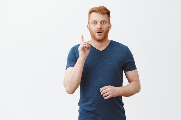 Ik heb het, heb een idee. knappe volwassen europese man met borstelharen in blauw t-shirt wijsvingers opheffen, hijgend, intens staren, suggestie geven of plan vertellen, eureka-gebaar tonen