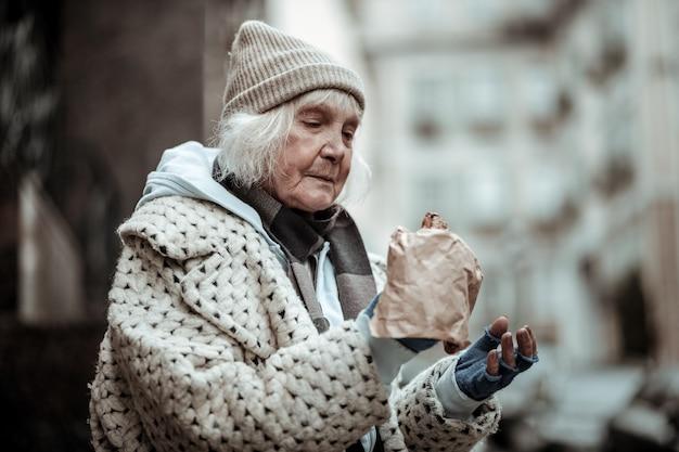 Ik heb honger. trieste oude vrouw die naar het eten kijkt terwijl ze erg honger heeft