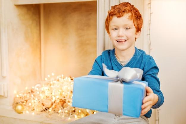 Ik heb iets voor je. vrolijke gekrulde jongen die lacht terwijl hij naast een decoratieve open haard zit en een prachtig ingepakt cadeau overhandigt.