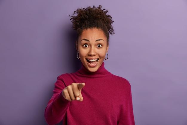 Ik heb je nodig. gelukkig krullend tienermeisje geeft met wijsvinger aan, kiest kandidaat, heeft een positieve verbaasde uitdrukking, lacht hardop, poseert over paarse muur, zegt ongelooflijk.
