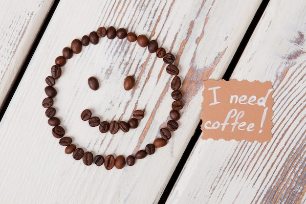 Ik heb koffie nodig. smileygezicht gemaakt van koffiebonen op witte houten ondergrond.