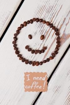 Ik heb koffieconcept nodig. koffiebonen gelukkig smileygezicht op wit hout.
