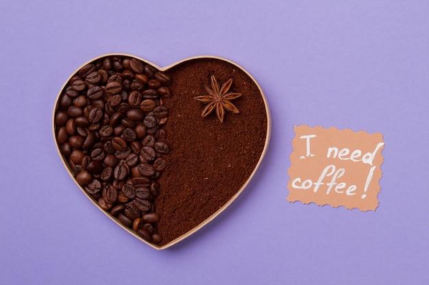 Ik heb koffieconcept nodig. koffiehart als kunst. koffiebonen en oploskoffiepoeder op paars oppervlak.