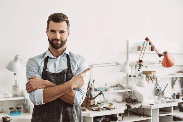 Ik heb mijn keuze gemaakt, en jij? portret van een vrolijke mannelijke juwelier met een schort, glimlachend en wijzende vinger naar copyspace terwijl hij in zijn sieradenstudio staat. bedrijf. sieraden workshop