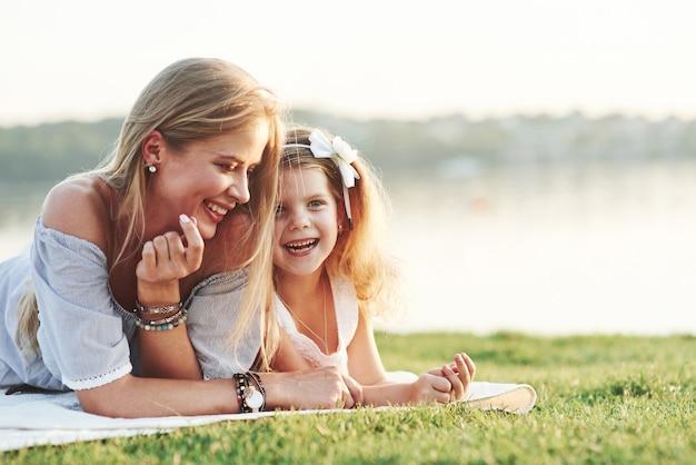 Ik heb net een grap gehoord. lachend. foto van jonge moeder en haar dochter die goede tijd hebben op het groene gras met meer bij achtergrond.