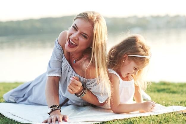 Ik heb net een grap gehoord. lachend. foto van jonge moeder en haar dochter die goede tijd hebben op het groene gras met meer bij achtergrond