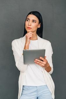 Ik heb online inspiratie nodig! mooie jonge peinzende vrouw die digitale tablet vasthoudt en wegkijkt terwijl ze tegen een grijze achtergrond staat