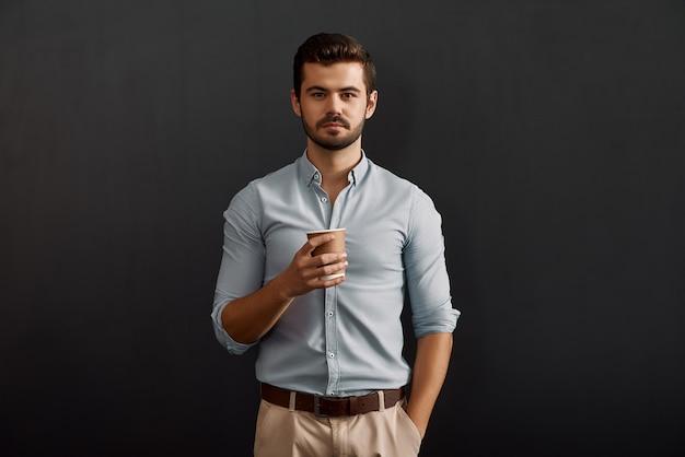 Ik heb wat rust nodig, jonge, bebaarde man die een kop warme koffie vasthoudt en kijkt