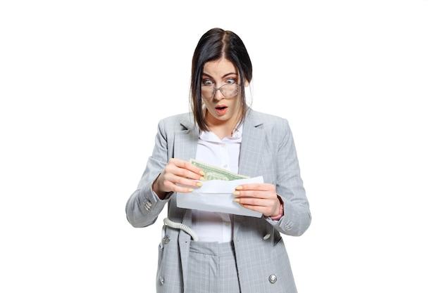 Ik hoop dat het maar een grap is. jonge vrouw in grijs pak die een klein salaris krijgt en haar ogen niet gelooft. geschokt en verontwaardigd. concept van de problemen, de zaken, de problemen en de spanning van de beambte.