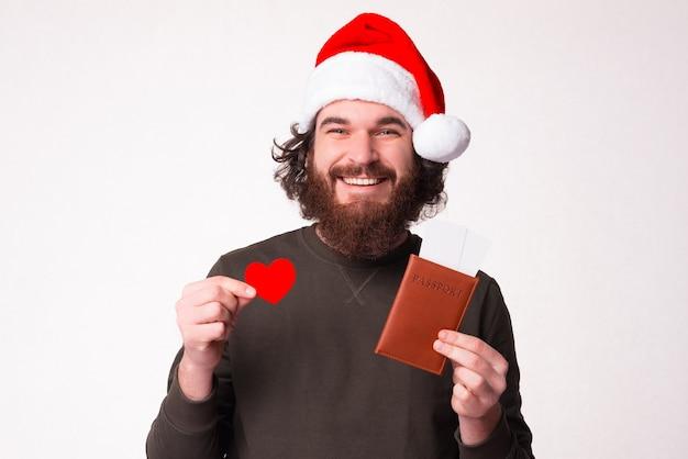Ik hou gewoon van reizen. bebaarde man houdt zijn paspoort met kaartjes en hartvorm.