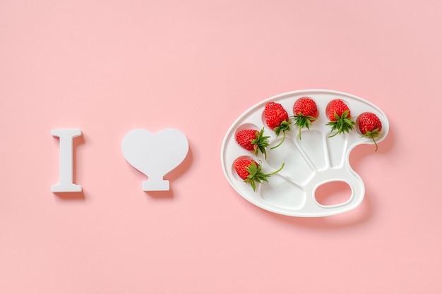 Ik hou van aardbeien, rode rijpe bessen op artistiek palet op roze papier