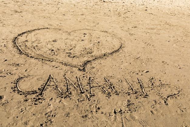 Ik hou van canarias. tekeningen in het zand op het strand van puerto rico in gran canaria, spanje.