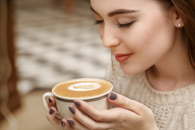 Ik hou van de geur. close-up shot van een prachtige jonge vrouw die haar koffie ruikt vrolijk glimlachend