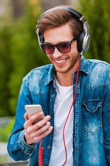Ik hou van dit liedje! gelukkige jonge man in koptelefoon met mobiele telefoon en glimlachend