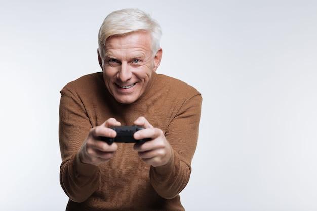 Ik hou van gamen. vrolijke senior man spelen van een videogame en lachend op grijs