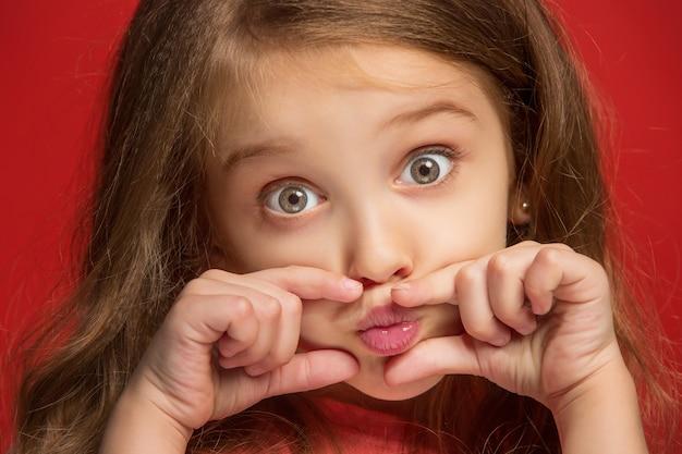 Ik hou van je. gelukkig tiener meisje permanent, glimlachend geïsoleerd op trendy rode studio achtergrond.